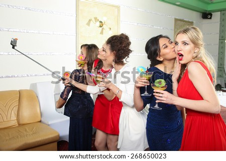 girls clinking glasses of cocktails at the party - stock photo