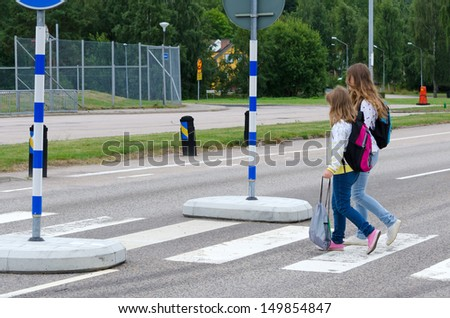Girls crossing the street on the way to school - stock photo