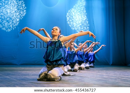 Girls dancers depicts the bird and puts his hands up, they smile. Modern choreography, performance - Russia, Abakan, choreography Festival, October 25, 2015 - stock photo