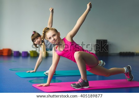 Girls doing gymnastic exercises or exercising in fitness class - stock photo