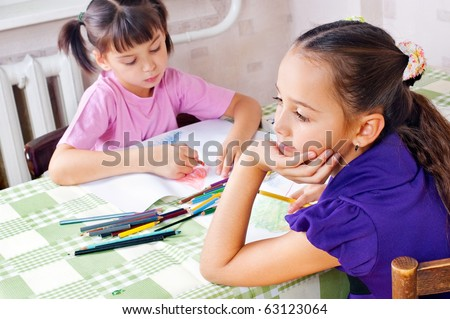 Girls drawing with crayons at the table - stock photo
