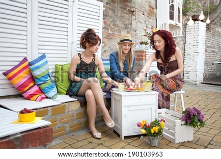 Girls enjoy lemonade and cupcakes  - stock photo