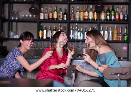 girls enjoying a drink in a bar - stock photo
