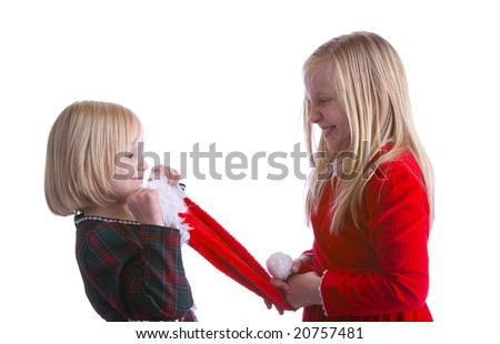 Girls fighting over a santa hat in Christmas dresses - stock photo