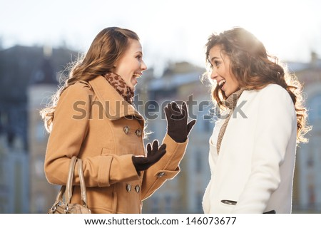 Girls gossiping. Two beautiful young women gossiping while standing outdoors - stock photo