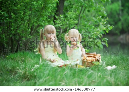 Girls have picnic at the lake with milk and buns - stock photo