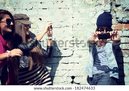 Girls having fun together outdoors and making photo with smart phone, lifestyle, toned and noise added - stock photo