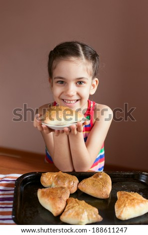 Girls holding baked pies and smiling. Cooking pies at home or  learning at culinary class. - stock photo