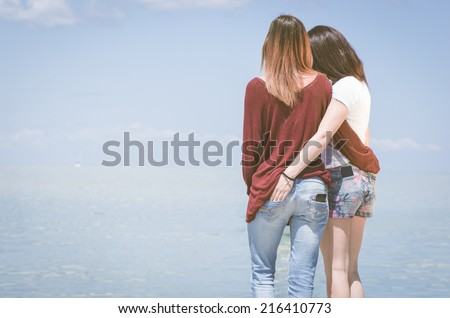 girls hugging on the pier - stock photo