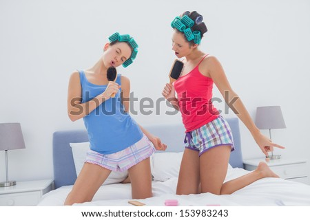 Girls in hair rollers singing with hairbrush in bed at sleepover - stock photo
