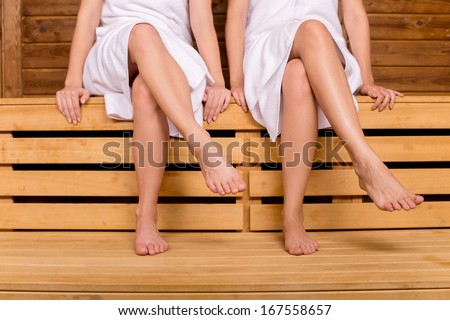 Girls in sauna. Cropped image of female legs in sauna - stock photo