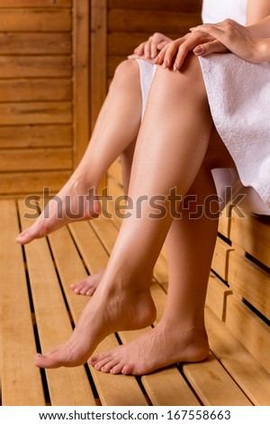 Girls in sauna. Cropped side view image of female legs in sauna - stock photo