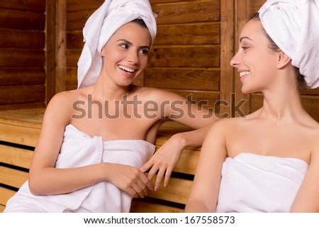Girls in sauna. Two attractive women wrapped in towel talking to each other and smiling while relaxing in sauna - stock photo