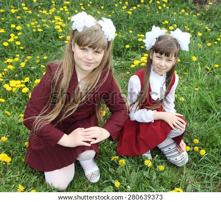 Girls in school uniform on the background of grass and dandelions - stock photo