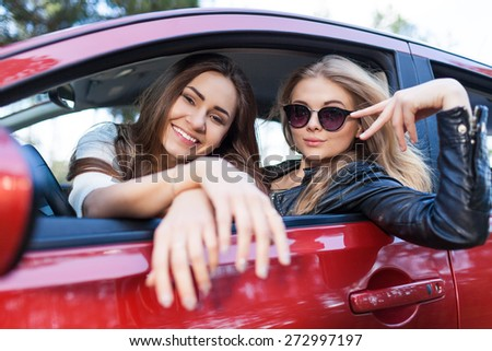Girls in the red car. Little holiday trip of friends - stock photo