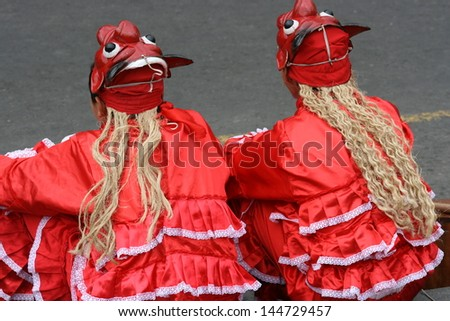 Girls in traditional Peruvian dress wear devil masks at a festival in the Plaza Mayor, in Lima, Peru - stock photo