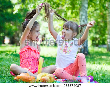 Girls kids sisters friends teasing showing off  tongues, sitting on grass - stock photo