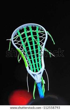 Girls lacrosse stick held up against the night sky during a night game. - stock photo