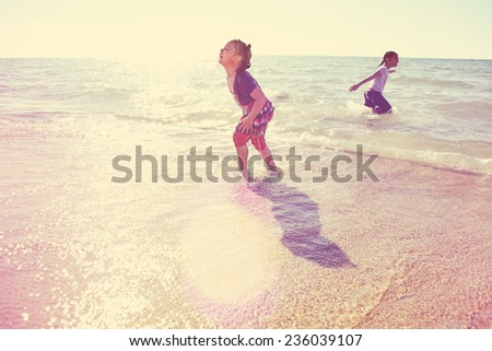 Girls laughing and playing in the waves at the beach.  Instagram effect - stock photo