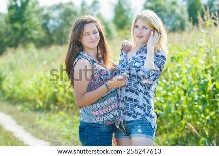 Girls listening to the music with one headphones for two - stock photo