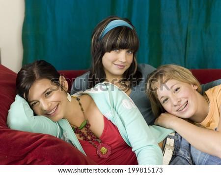 Girls lying on sofa - stock photo