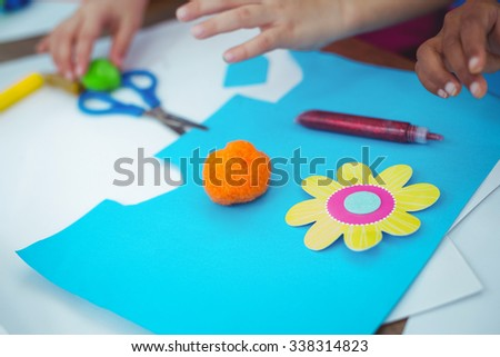 Girls making arts and crafts together at their desk - stock photo