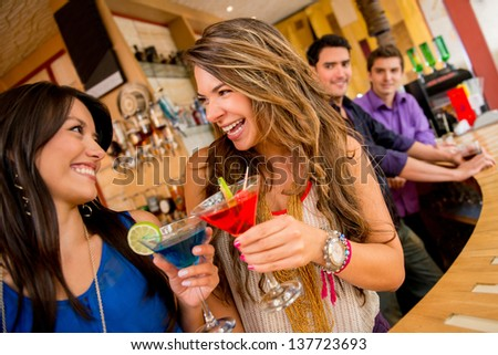 Girls night out having drinks and two men checking them out - stock photo