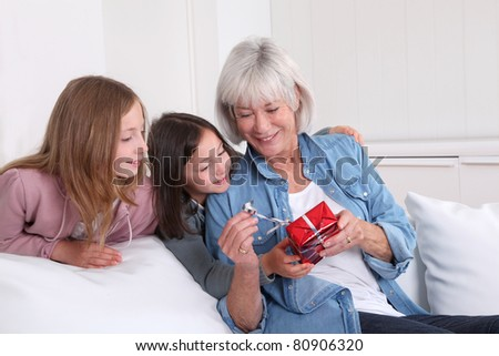Girls offering present to grandmother - stock photo