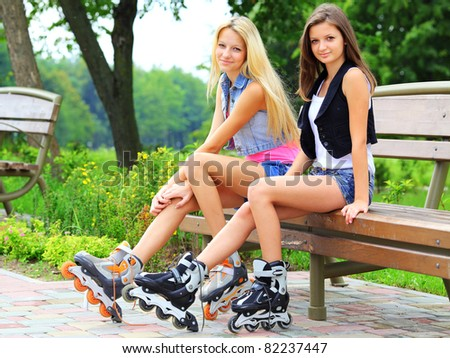 Girls on bench with rollers - stock photo