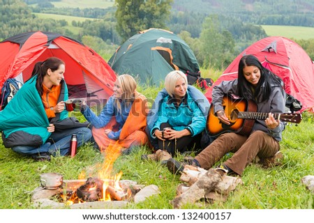 Girls on vacation camping with tents listening girl playing guitar - stock photo