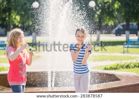 girls play at the fountain - stock photo