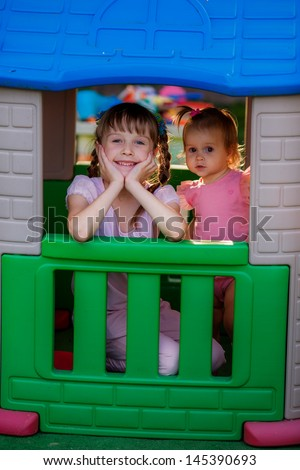 girls play in the children's house at the playground - stock photo