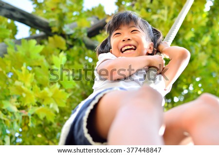 Girls play on the playground equipment in the park - stock photo