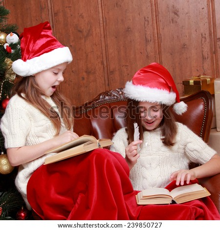 girls reading in a book near the christmas tree on Holiday theme/Charming kids reading books on Christmas time - stock photo