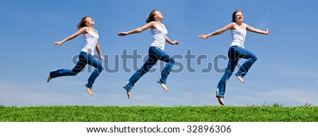 Girls run on a green grass against the blue sky - stock photo