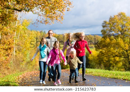 Girls running ahead at family walk through the park in fall or autumn - stock photo