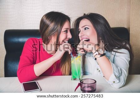 Girls share fruit cocktail - stock photo