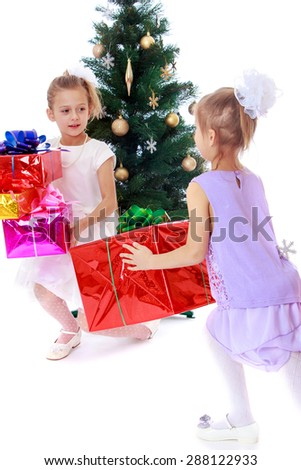 Girls sisters around the Christmas tree fuss considering boxes with gifts-isolated on white background - stock photo