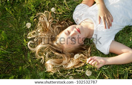 Girls sleeping in a field of grass with dandelions - stock photo