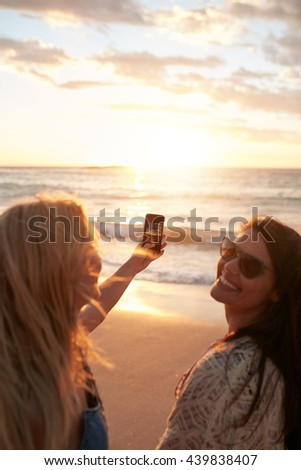 Girls taking a photo of the sunset with mobile phone. Two young women with mobile phone taking pictures of a sunset at the seaside. - stock photo