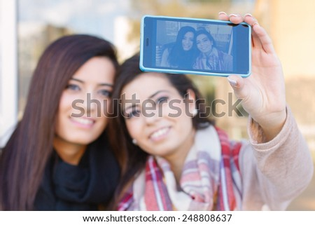 Girls taking a Selfie. Selective focus on Smartphone - stock photo