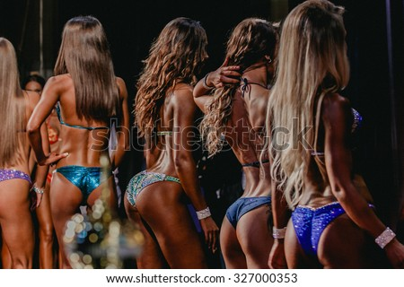 girls to compete in fitness bikini. Side view of female buttocks - stock photo