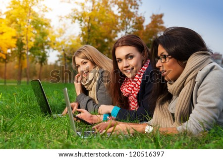 Girls using wifi internet in college park - stock photo