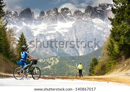 Girls with bikes are on the road in the woods and mountains of the Dolomites. Italy. - stock photo