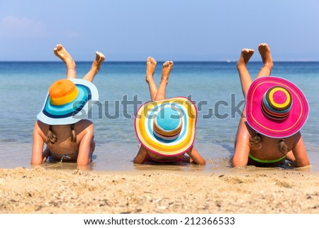Girls with colorful hats on the beach - stock photo