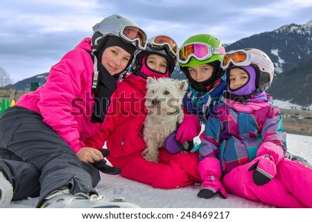 Girls with dog on the ski vacation - stock photo