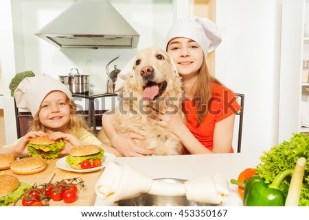 Girls with their pet in cook's hats preparing meal - stock photo