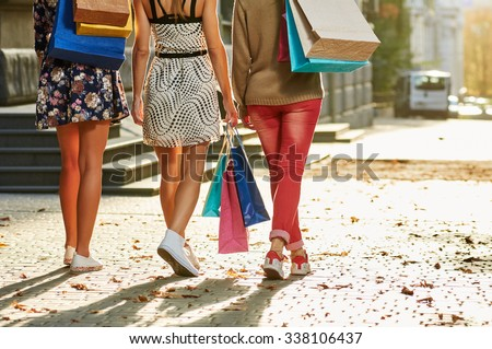 girls women friends with sexy legs walking. from back. with shopping bags - stock photo