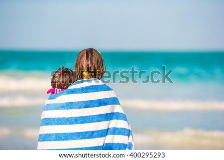 Girls wrapped in towel at tropical beach in the evening - stock photo