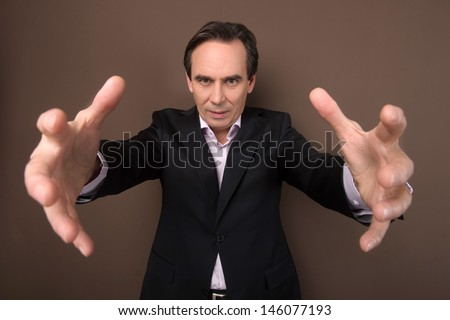 Give it all to me! Confident mature businessman trying to grab something with his hands outstretched and looking at camera - stock photo